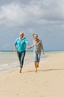 mature couple running hand in hand on beach