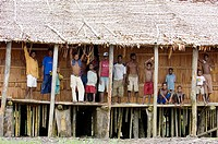 Papuan men standing in front of traditional house, Indonesia
