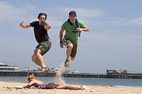 Men jumping over sunbathing woman