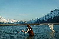 Man fishing with net in lake