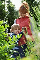 Mother embracing son 5-6 in garden (thumbnail)