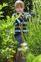 Boy 5-6 with spade surrounded by plants portrait (thumbnail)