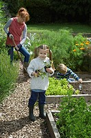 Mother gardening with two children 5_6 in countryside