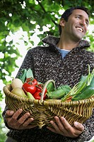 Man holding fruit and vegetable basket outdoors