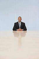 Business man sitting at end of conference table portrait