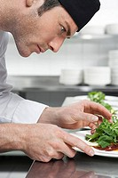 Male chef preparing salad in kitchen close_up
