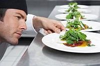 Male chef preparing salad in kitchen close-up (thumbnail)
