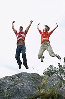 Couple leaping with arms raised over rock
