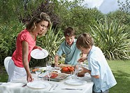 Mother and two sons 6_11 laying dinner table in garden