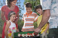 Family with three children 6_11 grilling in garden