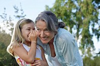 Young blonde girl whispering in grandmother´s ear