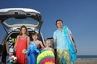 Portrait of family with three children 3-11 at beach by car (thumbnail)