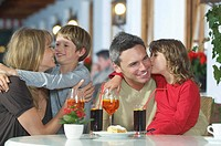 Parents and children 7-9 with drinks embracing at restaurant (thumbnail)