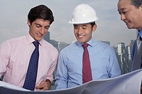 Business men and construction site manager reading blueprints