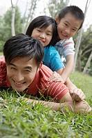 Father with son and daughter 7-9 lying in grass in park (thumbnail)
