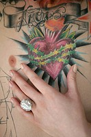 Female hand against a tattooed chest