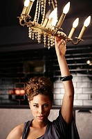 Young ethnic woman holding a chandelier
