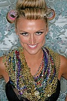 Woman smiling wearing beaded necklace and curlers looking at camera