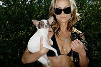 Woman in bikini holding two dogs