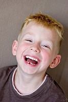 A five-year-old blonde, blue-eyed boy is laughing, showing a gap where he has lost a tooth. He is wearing a brown t-shirt and is standing in front of ...