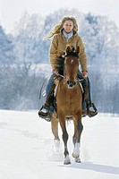 Young lady riding western_style on back of an Arabian horse at winter