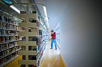 Man standing by bookshelves in a library