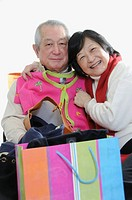 Senior asian couple having fun shopping