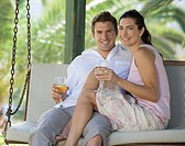 A couple drinking wine on a swing
