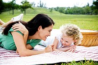 mother and daughter lying on picnic rug