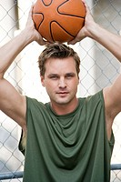 Man in a green vest holding a basketball above his head