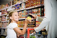 Young girl helping her mother in a supermarket