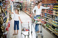 Woman and a young girl with a shopping trolley walking down a supermarket aisle