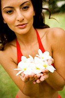 Beauty portrait of a woman in a tropical setting holding frangipani
