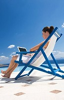 A woman sitting on a deck chair using a laptop (thumbnail)
