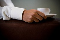 Close up of a man holding an espresso cup