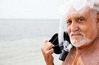 Senior man with snorkel gear and flippers at the beach