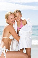 Mother embracing daughter on the beach
