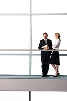 Businessman and woman talking in modern office building