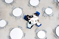 Overhead view of informal business meeting at table of staff canteen