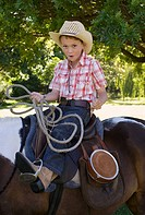 A boy riding a horse and holding a lasso