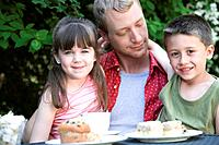 Father and children eating outdoors