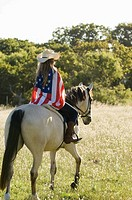 A girl riding a horse wearing an american flag