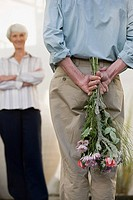 A senior man hiding flowers behind his back