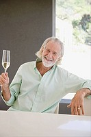 A senior man holding a glass of champagne