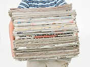 Boy carrying a stack of newspapers