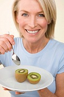 A woman holding kiwi on a plate