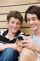 Teenage boys using a cell phone