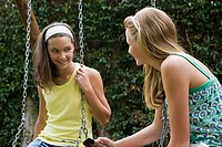 Teenage girls sat on swings