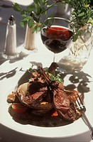 Plated meat dish with red wine set on a table outdoors