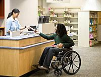 African man in wheelchair at library (thumbnail)